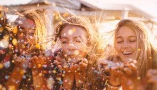 Üç sarışın kadın, avuçlarındaki rengarenk konfetileri üflüyor.