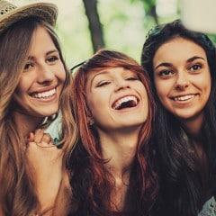 Gülümseyen ve cep telefonuna bakan, dalgalı saçlara sahip arkadaşlar.