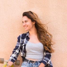 Elindeki kaykayı ile gülümseyen, dalgalı uzun saçlı bir kadın.